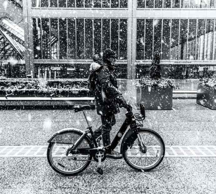 A bike commuter wearing street clothes in the snow walking with a bikeshare bike.