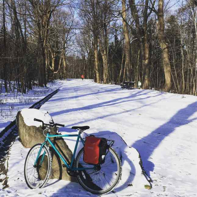 Riding along a snow packed road in Montreal. This bike has one studded tire on the front and a normal tire on the back, and of course a rear rack with pannier!