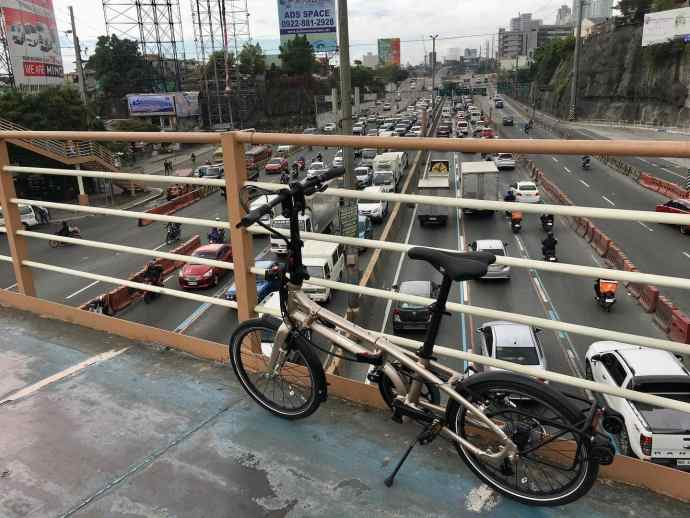 folding brompton bicycle on a bridge above a highway in Manilla.