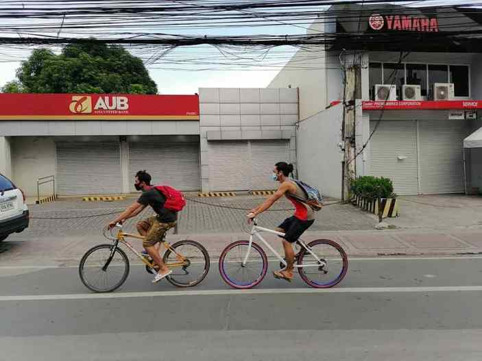 two bike commuters riding down the street in pasig city, manila with their face masks on