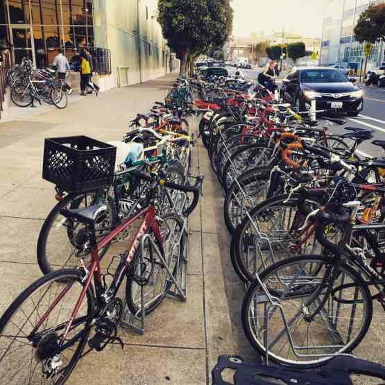 lots of different commuter bicycles parked on a san francisco street
