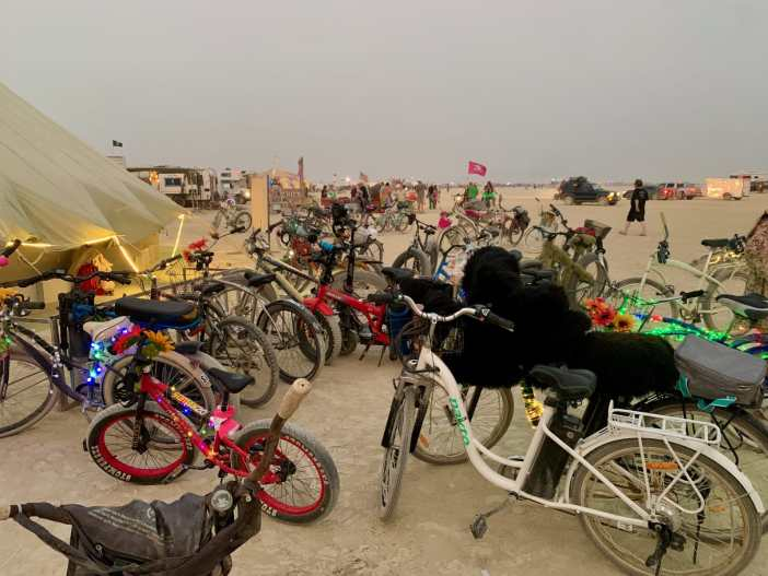 many decorated bicycles parked outside of a theme camp in black rock city desert of burning man