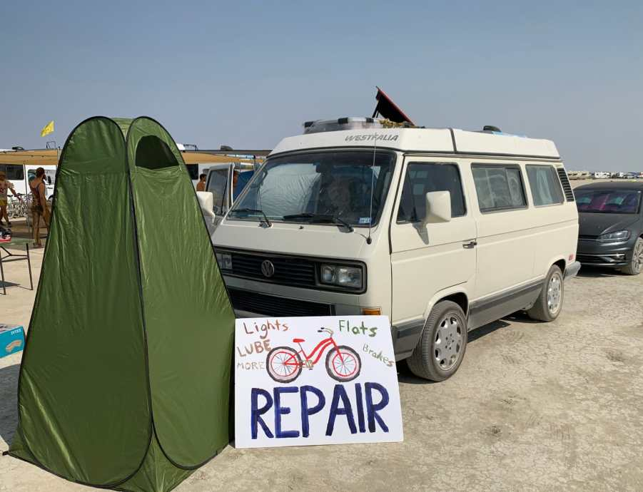 A camp setup with a Bike Repair sign in front of a vw vanagon and a pop up privacy tent