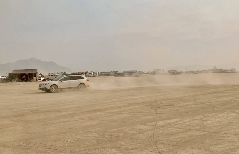 A car leaving behind a trail of dust on the playa of burning man