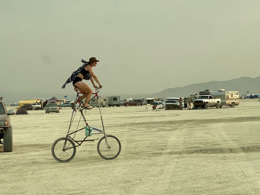 someone riding a double decker tall bicycle on the black rock city desert at burning man