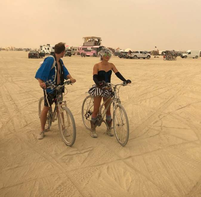 two burners dressed up and on their bicycles, ready for a bike ride through the soft sand of the playa