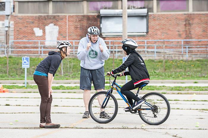 BikeWalkKC Education Outreach Coordinator, Laura, and East teacher, Mr. Patrick Brier, coaching a student on hazard maneuvers.