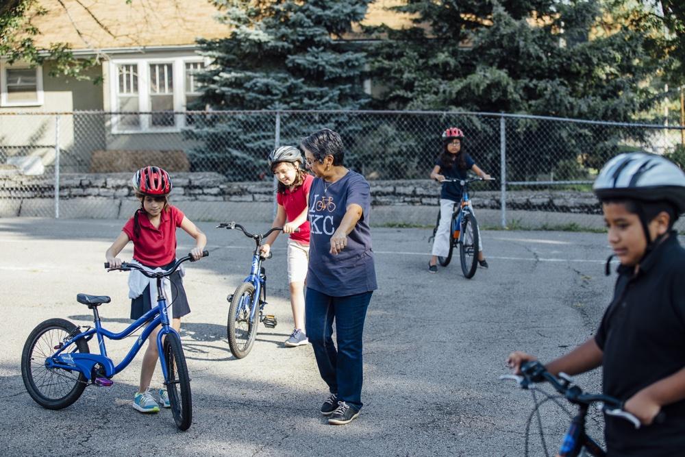 Image of woman teaching kids on bikes.