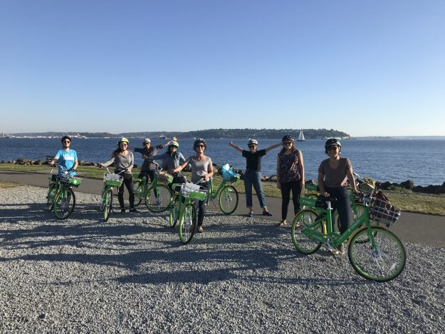 A group of cyclists poses with green lime bikes on a beach with mountains and water in the background.