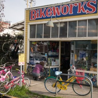 The exterior of the Bike Works bike shop - a yellow house with several bikes parked outside and the Bike Works sign in red letters on a blue background across the top of the building.
