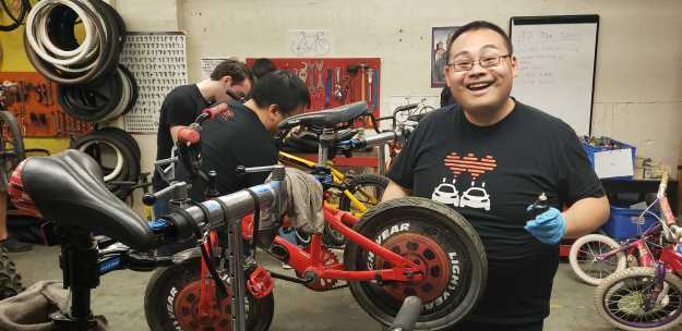 A volunteer smiles at the camera while working on a red kid's bike in a bike stand