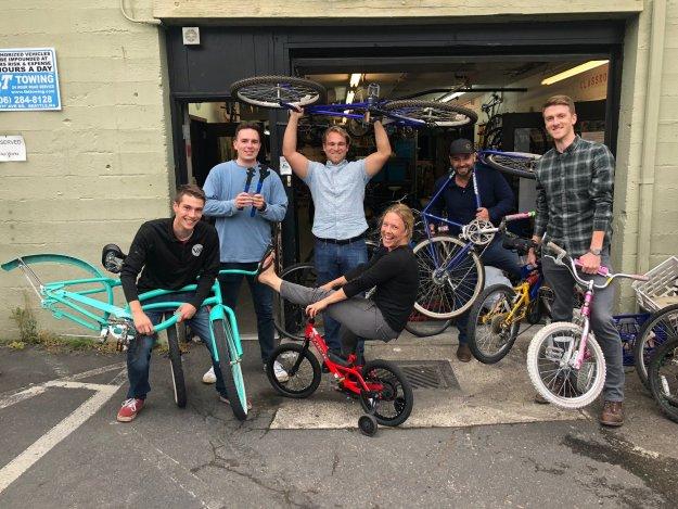 A group of 5 happy volunteers pose in front of an open garage door holding recently refurbished kids' bikes.