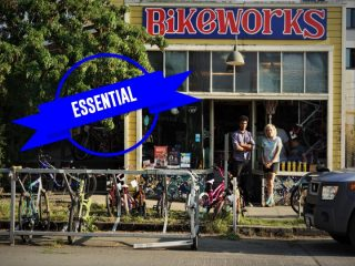 The exterior of the Bike Works shop with the words Essential in blue overlaying the image.