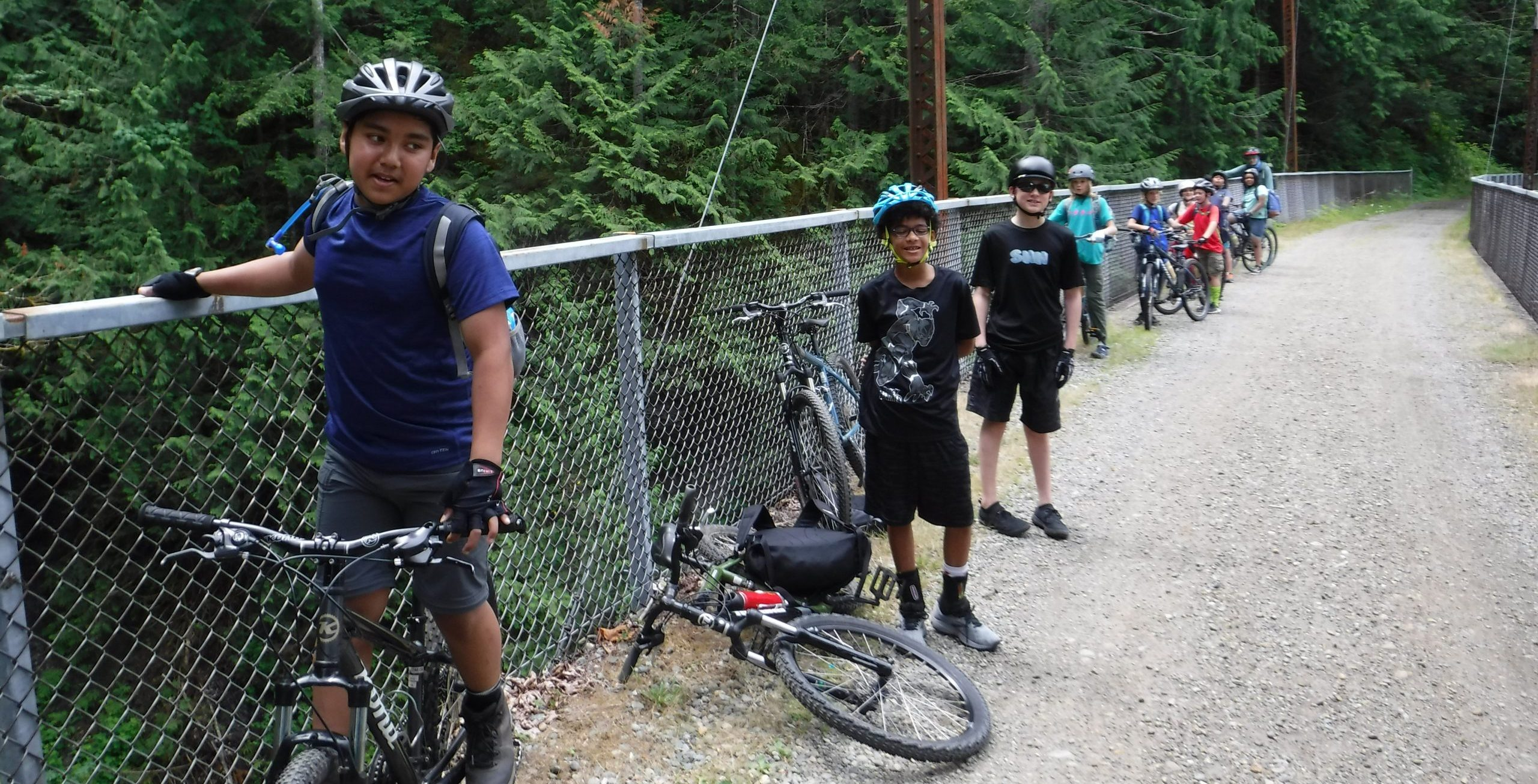 Ten youth riders with their bicycles lined up against a chain link fence bordering a gravel path