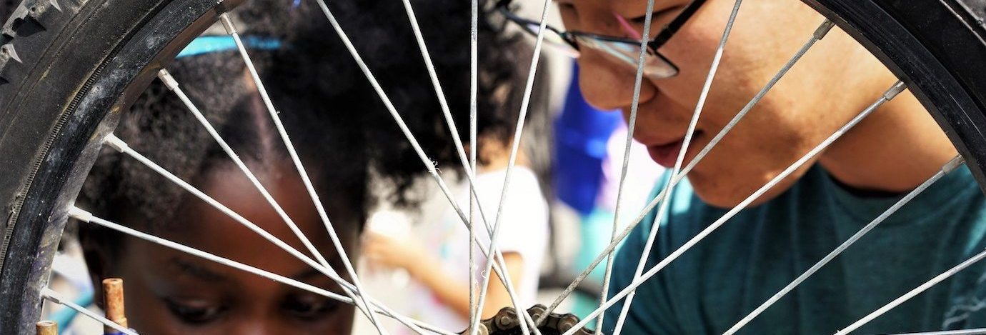 Two youth inspect the rear wheel bug of a bike. The bike wheel is in front of their faces and framed by the spokes.