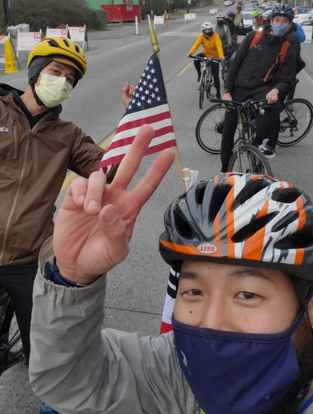 Two helmeted cyclists in masks take a selfie while flashing the peace sign and waiving an American flag