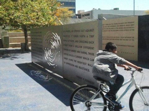 A boy on a bike circles the moving memorial to Robert F. Kennedy in front of the former Ambassador Hotel.