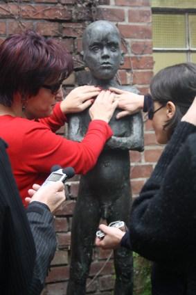Zwei Frauen, eine mit Sonnenbrille, eine mit verbundenen Augen betasten die Bronzeplastik eines nackten Jungen