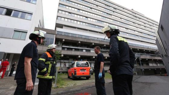 Feuerwehrleute stehen vor dem Behörden-Hochhaus an der Hamburger Straße