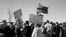 Am 22. November 1963, dem Tag seiner Ermordung, warten Kennedy-Gegner auf dem Flughafen von Dallas auf die Ankunft des Präsidenten.
