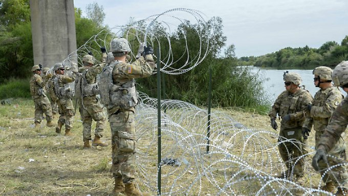 US soldiers pull a fence on the Mexican border.
