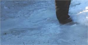Gående person sätter ned en fot på isigt och ojämnt underlag