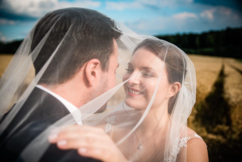 Braut und Bräutigam unterm Schleier auf ihrer Hochzeit in der Wipperaue Solingen