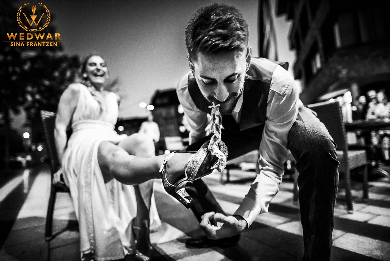 Bräutigam ergattert mit den Zähnen das Strumpfband seiner Braut - Gewinnerbild Wedwar Award - Hochzeitsfotografin Sina Frantzen bildsprache Remscheid