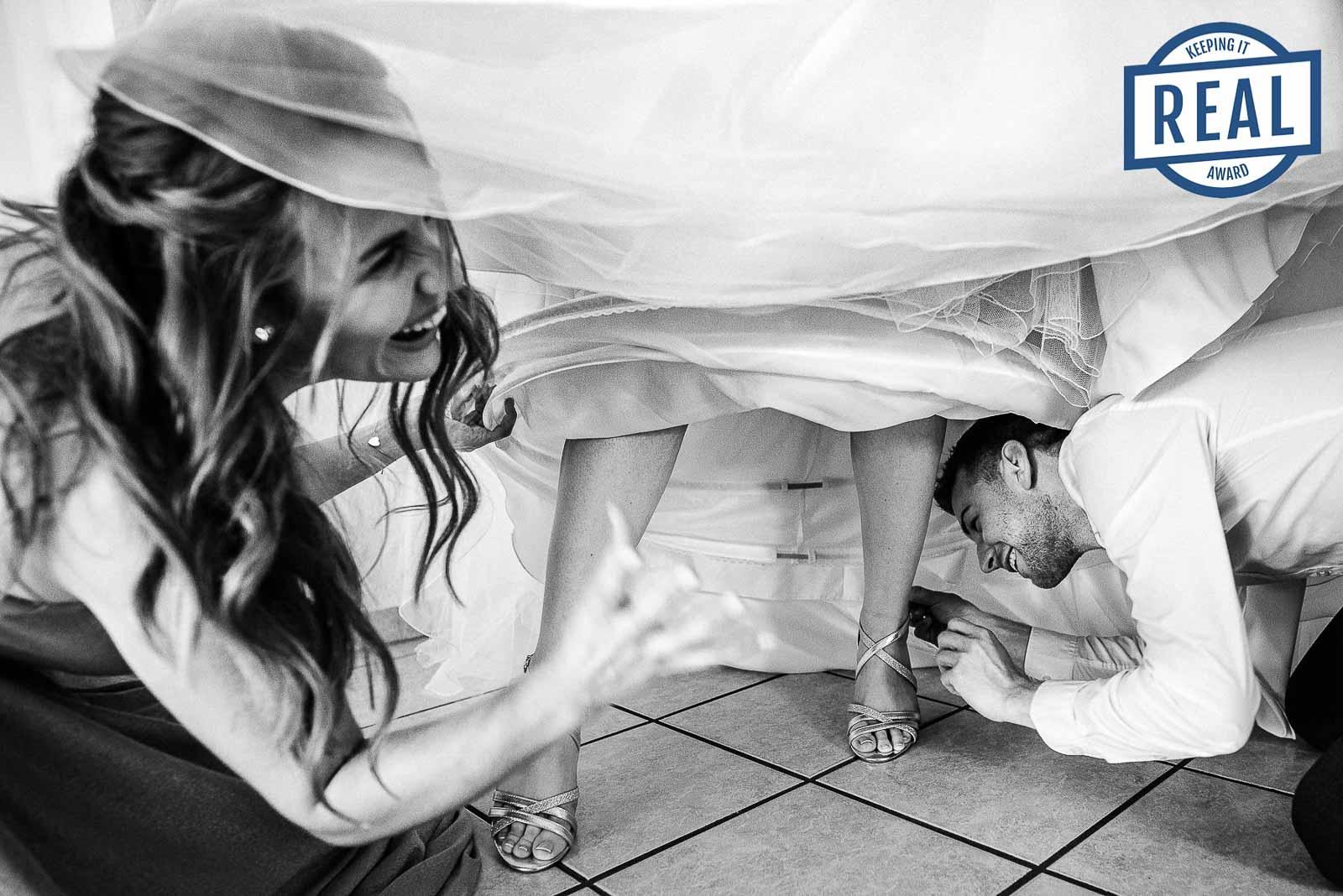 Freunde der Braut helfen bei den Brautschuhen unter dem Brautkleid. - Gewinnerbild Photographers Keeping it Real Summer Awards 2021 - Hochzeitsfotografin Sina Frantzen bildsprache Remscheid