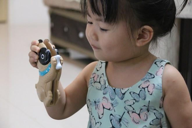 教鰻魚如何正確使用可愛動物夾。記住:讓孩子小手從下面抓住小狗的腳會比較容易使用。