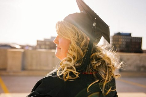 college graduate silhouetted by the sun.
