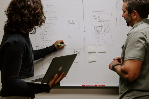 Two people collaborating at a white board.