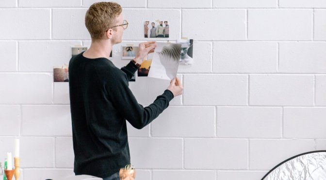 Person pinning photos on a wall.