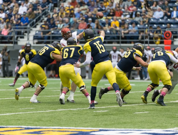 NAU quarterback Chase Cartwright releases a pass toward receiver Ify Umodu