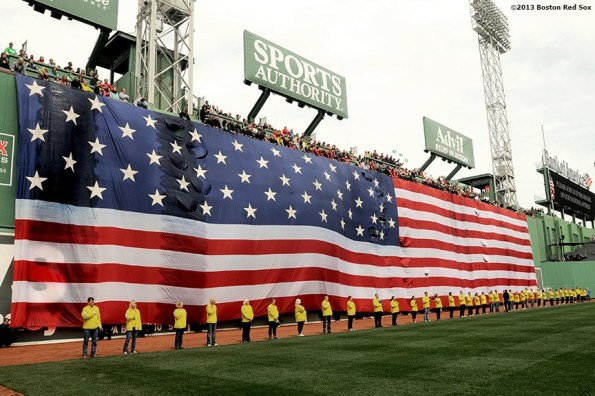 """""""Marathon Volunteers stand in front of the American Flag on the Green Monster during a pre-game ceremony honoring the victims, first responders, and others involved in the attacks on the 2013 Boston Marathon Saturday, April 20, 2013."""""""