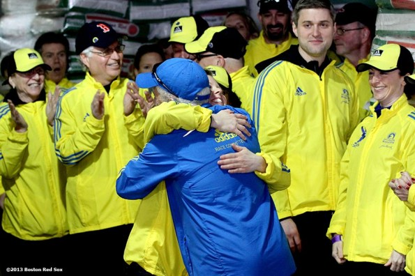 """""""Marathon Volunteer Tinamarie Sanborn of Somerville, Massachusetts gives a birthday hug to Tom Licciardello of North Andover, Massachusetts during a pre-game ceremony honoring the victims, first responders, and others involved in the attacks on the 2013 Boston Marathon Saturday, April 20, 2013."""""""