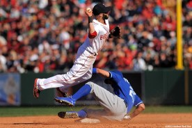 """""""Boston Red Sox second baseman Dustin Pedroia turns a double play during the eighth inning of a game against the Kansas City Royals Sunday, April 21, 2013 at Fenway Park in Boston, Massachusetts."""""""