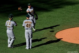 """""""Oakland Athletics shortstop Jed Lowrie tosses a glove to catcher Derek Norris during a game against the Boston Red Sox Wednesday, April 24, 2013 at Fenway Park in Boston, Massachusetts."""""""