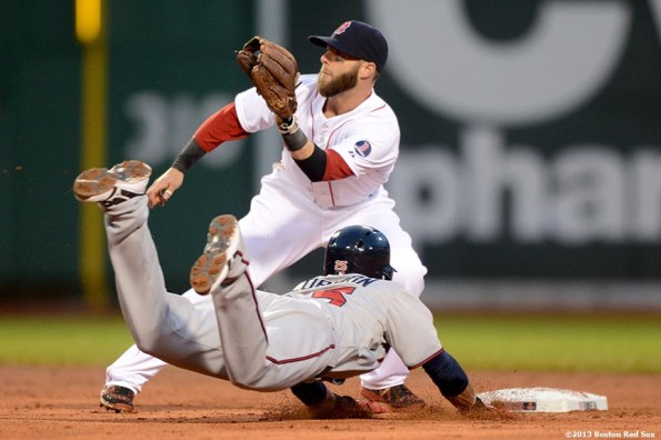 """""""Boston Red Sox second baseman Dustin Pedroia applies a tag on Minnesota shortstop Pedro Florimon as he steals second base during the second inning of a game against the Minnesota Twins Thursday, May 9, 2013 at Fenway Park."""""""