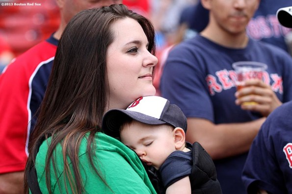 """""""A mother holds her son as he sleeps before a game between the Boston Red Sox and the Toronto Blue Jays Sunday, May 12, 2013  on Mother's Day at Fenway Park in Boston, Massachusetts."""""""