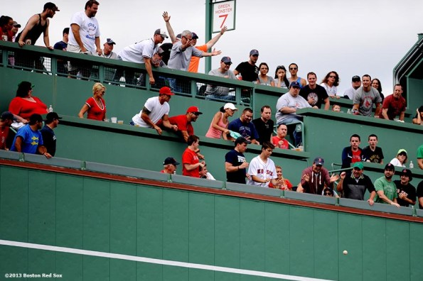 """""""Fans cheer as a ball bounces off the green monster during a game between the Boston Red Sox and the Los Angeles Angels of Anaheim Saturday, June 8, 2013 at Fenway Park in Boston, Massachusetts."""""""