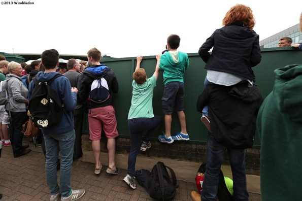 """""""Young fans climb a wall to get a better view of No. 14 Court at the All England Lawn and Tennis Club in London, England Friday, June 28, 2013 during the 2013 Championships Wimbledon."""""""