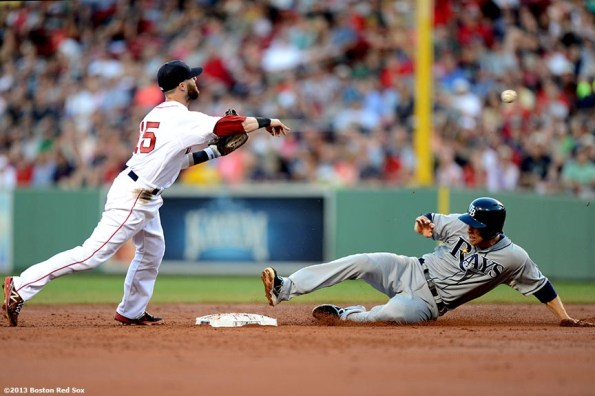 """""""Boston Red Sox second baseman Dustin Pedroia turns a double play over second baseman Ben Zobrist during the third inning of a game against the Tampa Bay Rays Monday, July 29, 2013 at Fenway Park in Boston, Massachusetts."""""""