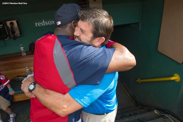"""""""Former Boston Red Sox catcher Jason Varitek hugs designated hitter David Ortiz in the dugout before a game against the Seattle Mariners Tuesday, July 30, 2013 at Fenway Park in Boston, Massachusetts."""""""