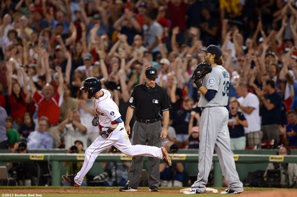"""""""Boston Red Sox second baseman Dustin Pedroia rounds first base after a two-run home run during to give the Red sox a 4-3 lead during the seventh inning of a game against the Seattle Mariners Wednesday, July 31, 2013 at Fenway Park in Boston, Massachusetts."""""""