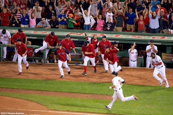 """""""Boston Red Sox teammates celebrate as shortstop Stephen Drew runs to first base after hitting the game winning RBI single with the bases loaded during the bottom of the fifteenth inning of a game against the Seattle Mariners Thursday, August 1, 2013 at Fenway Park in Boston, Massachusetts."""""""