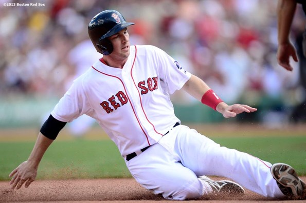 """""""Boston Red Sox shortstop Stephen Drew slides into third base on a hit and run play during the fifth inning of a game against the Arizona Diamondbacks Sunday, August 4, 2013 at Fenway Park in Boston, Massachusetts."""""""