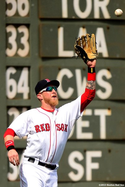 """""""Boston Red Sox left fielder Mike Carp catches a fly ball during the sixth inning of a game against the Arizona Diamondbacks Sunday, August 4, 2013 at Fenway Park in Boston, Massachusetts."""""""