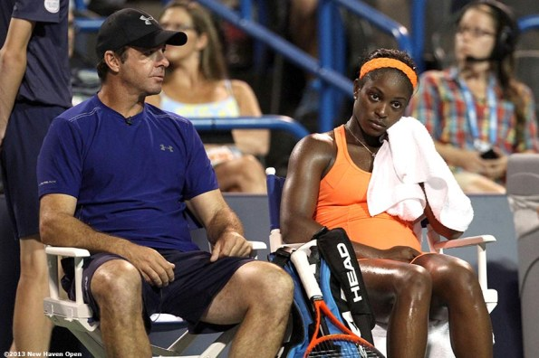 """""""Sloane Stephens reacts on a changeover during a match against Caroline Wozniacki as her coach, David Nainkin, looks on on Day 7 of the New Haven Open at Yale University in New Haven, Connecticut Thursday, August 20, 2013."""""""