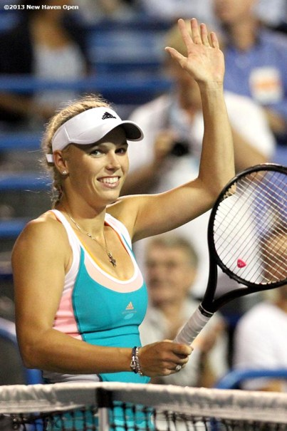 """""""Caroline Wozniacki waves to the crowd on Stadium Court after defeating Sloane Stephens on Day 7 of the New Haven Open at Yale University in New Haven, Connecticut Thursday, August 20, 2013."""""""
